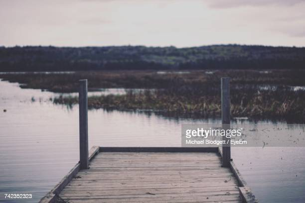 pier over lake against sky - michael blodgett stock pictures, royalty-free photos & images