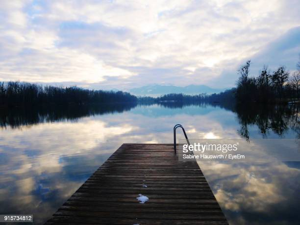 pier over lake against sky - sabine hauswirth stock pictures, royalty-free photos & images