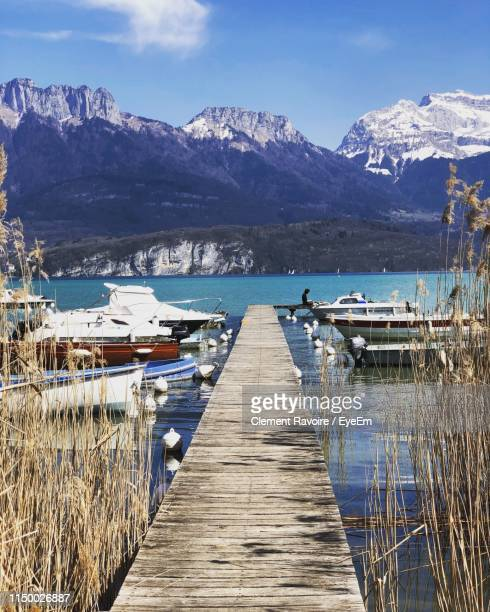 pier over lake by snowcapped mountains against sky - annecy photos et images de collection