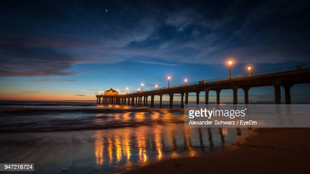 Pier Over River Against Cloudy Sky At Sunset