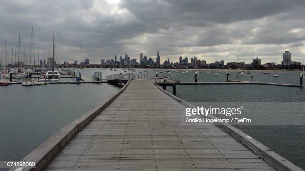 Pier Over River Amidst Buildings In City Against Sky