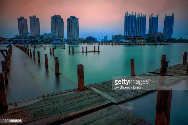 Pier Over River By Buildings Against Sky At Dusk