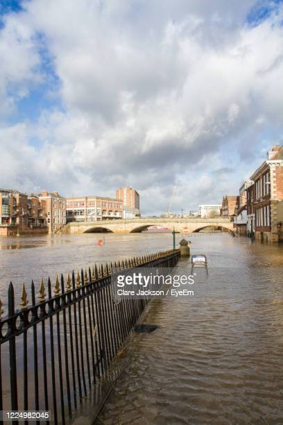 pier over river by buildings in city against sky - riverbank stock pictures, royalty-free photos & images