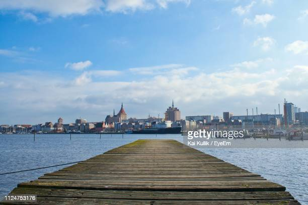 pier over river in city against blue sky - rostock stock pictures, royalty-free photos & images