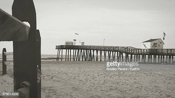 pier over sand at beach against sky - pavard stock pictures, royalty-free photos & images