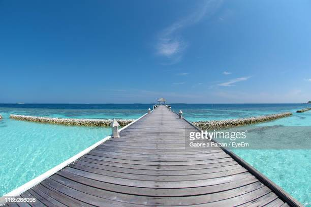 pier over sea against blue sky - gabriela stock pictures, royalty-free photos & images