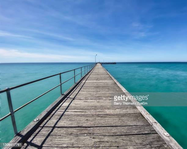 pier over sea against blue sky - barry wood stock pictures, royalty-free photos & images