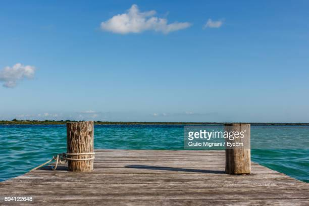 pier over sea against blue sky - molo foto e immagini stock