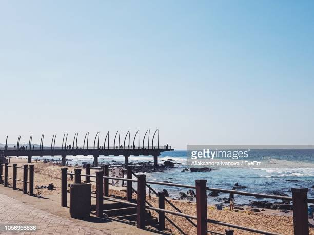 pier over sea against clear sky - durban beach stock photos and pictures