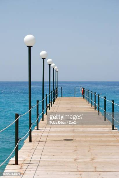pier over sea against clear sky - tolga erbay stock photos and pictures