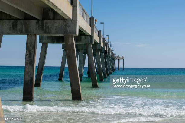pier over sea against clear sky - destin beach stock pictures, royalty-free photos & images