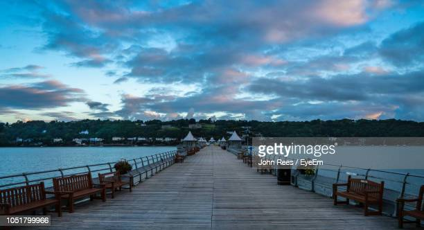 pier over sea against sky at dusk - bangor wales stock photos and pictures