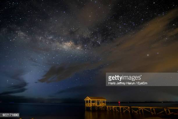 pier over sea against sky at night - kota kinabalu stock pictures, royalty-free photos & images