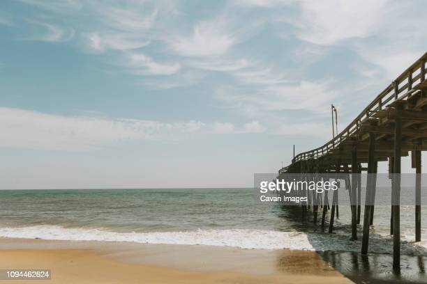 pier over sea against sky during sunny day - outer banks stock pictures, royalty-free photos & images
