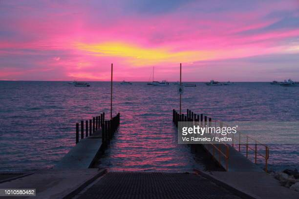 pier over sea against sky during sunset - ratnieks stock pictures, royalty-free photos & images