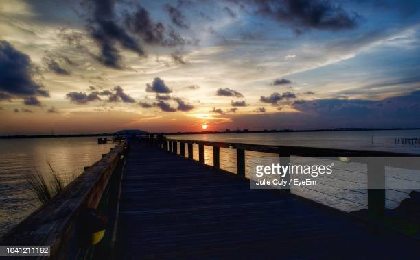 pier over sea against sky during sunset - julie culy stock pictures, royalty-free photos & images