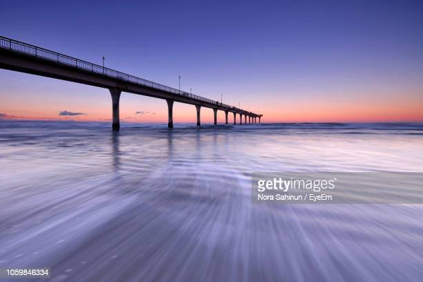 pier over sea against sky during sunset - christchurch stock pictures, royalty-free photos & images