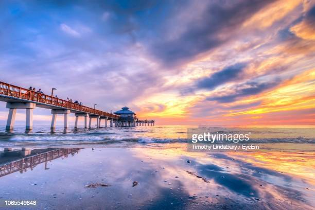pier over sea against sky during sunset - fort myers beach stock pictures, royalty-free photos & images
