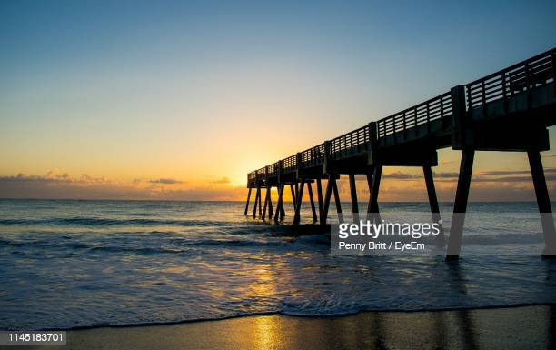 pier over sea against sky during sunset - vero beach stock pictures, royalty-free photos & images