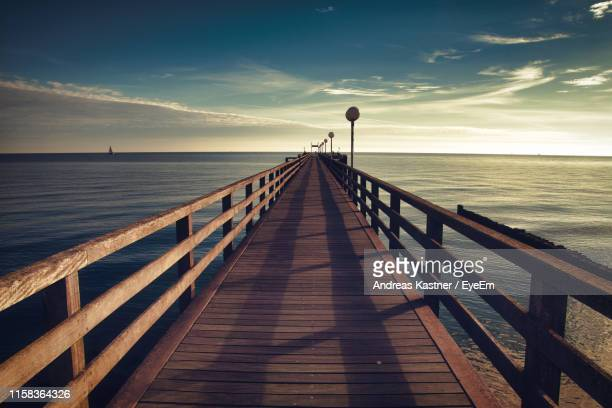 pier over sea against sky during sunset - pier stock pictures, royalty-free photos & images