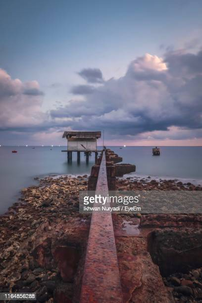 pier over sea against sky during sunset - banda aceh stock pictures, royalty-free photos & images