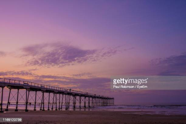 pier over sea against sky during sunset - north yorkshire stock pictures, royalty-free photos & images