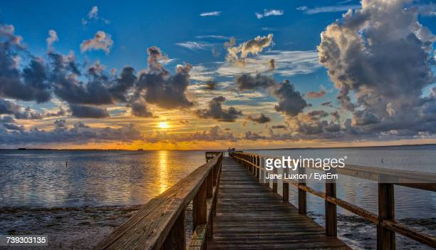 pier over sea against sky during sunset - palm harbor stock pictures, royalty-free photos & images