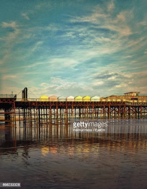 pier over sea against sky during sunset - hastings stock photos and pictures