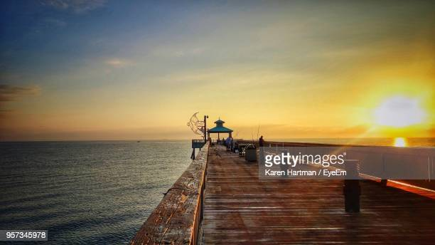 pier over sea against sky during sunset - delray beach stock photos and pictures