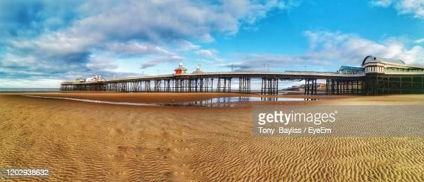 pier over sea against sky in blackpool - blackpool beach stock pictures, royalty-free photos & images