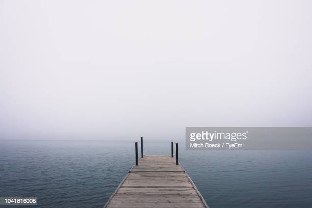 pier over sea against sky - jetty stock pictures, royalty-free photos & images