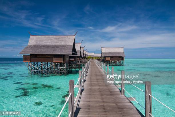 pier over sea against sky - sabah state stock pictures, royalty-free photos & images