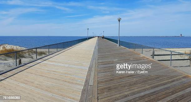 pier over sea against sky - boardwalk stock pictures, royalty-free photos & images