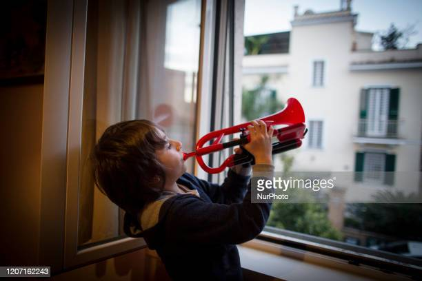 Pier Paolo, seven years old, plays trumpet from a window of his house during a music flash mob called ''Look out from the window, Rome mine !'' aimed...