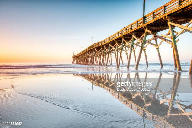 Pier reflecting in sea at sunrise