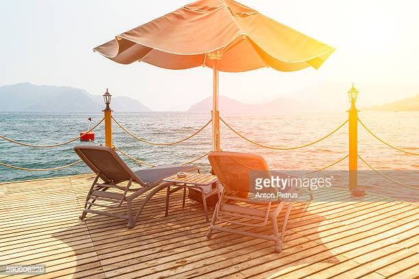 Pier with tables, chairs and parasols with calm sea