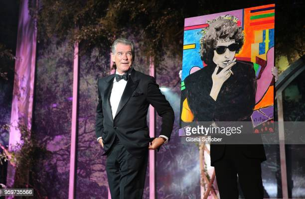 Pierce Brosnan with his paintin on stage at the amfAR Gala Cannes 2018 at Hotel du CapEdenRoc on May 17 2018 in Cap d'Antibes France