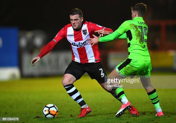 Pierce Sweeney of Exeter City is challenged by Charlie Cooper of Forest Green Rovers during the Emirates FA Cup Second Round Replay between Exeter...
