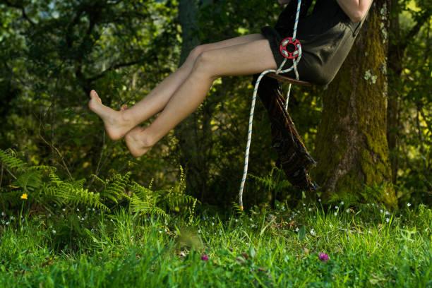 piernas de chica joven en un columpio en la naturaleza