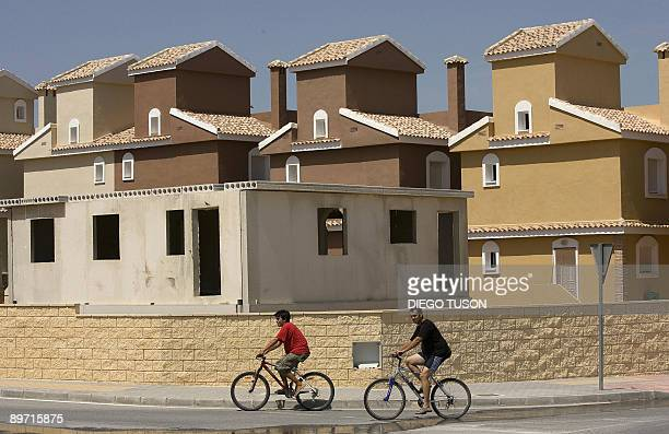 Pierre Ausseill People ride they bicycles past halfbuilt buildings and empty villas at the Montecid residential development area in Alicante on...