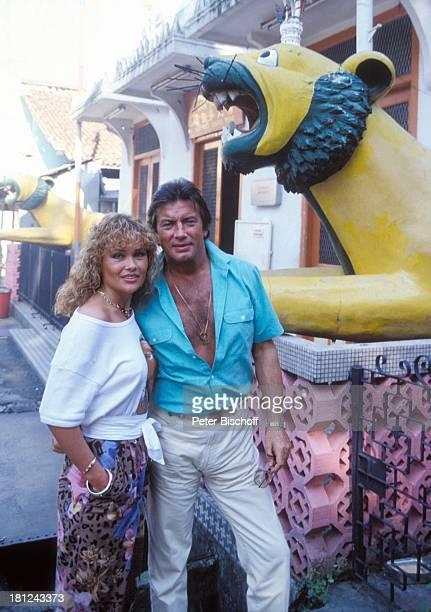 Pierre Brice Ehefrau Hella neben den Dreharbeiten zur ARDSerie Schoene Ferien Folge 5 Singapur/Malaysia Asien Palme chinesischer Figur Umarmung...