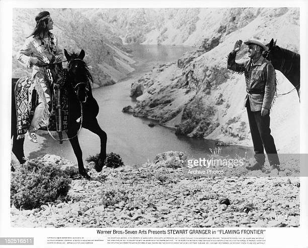 Pierre Brice pulling up on horseback to Stewart Granger in a scene from the film 'Flaming Frontier' 1965