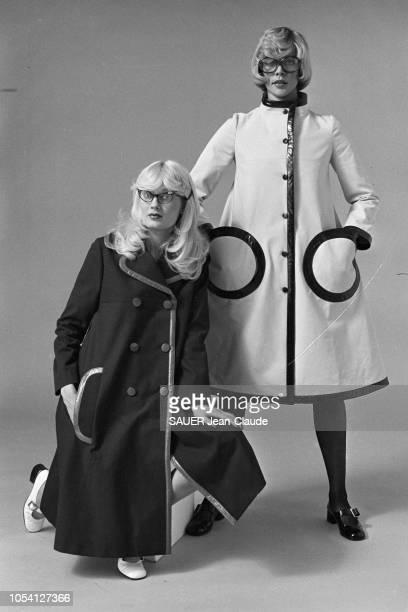 Pierre CARDIN présente les modèles de sa collection prêt à porter en janvier 1972 Deux mannequins présentant un manteau sombre à double boutonnage et...