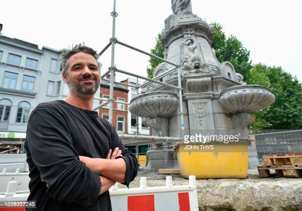 Pierre Deger the worker who found a small zinc casket containing the remains of a former mayor is pictured in front of the ornate fountain covered...