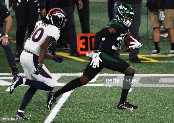 Pierre Desir of the New York Jets runs back an interception for a touchdown against Jerry Jeudy of the Denver Broncos during the fourth quarter at...