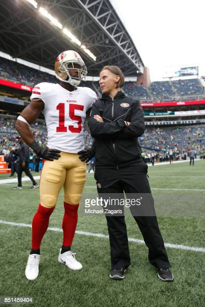 Pierre Garcon and Offensive Assistant Coach Katie Sowers of the San Francisco 49ers talk on the field prior to the game against the Seattle Seahawks...