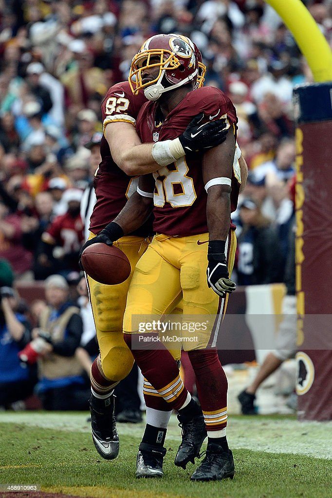 Pierre Garcon #88 celebrates with Logan Paulsen #82 of the Washington Redskins after scoring a touchdown in the third quarter during an NFL game against the Dallas Cowboys at FedExField on December 22, 2013 in Landover, Maryland.