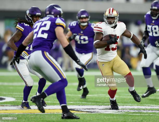Pierre Garcon of the San Francisco 49ers carries the ball against Trae Waynes and Harrison Smith the Minnesota Vikings during the first quarter in...