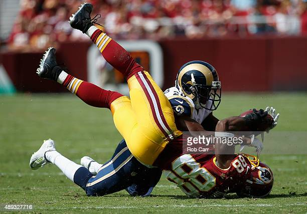 Pierre Garcon of the Washington Redskins catches a pass in front of Lamarcus Joyner of the St Louis Rams in the first half at FedExField on September...