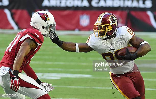 Pierre Garcon of the Washington Redskins runs with the ball and straight arms defender Marcus Cooper of the Arizona Cardinals during the second...